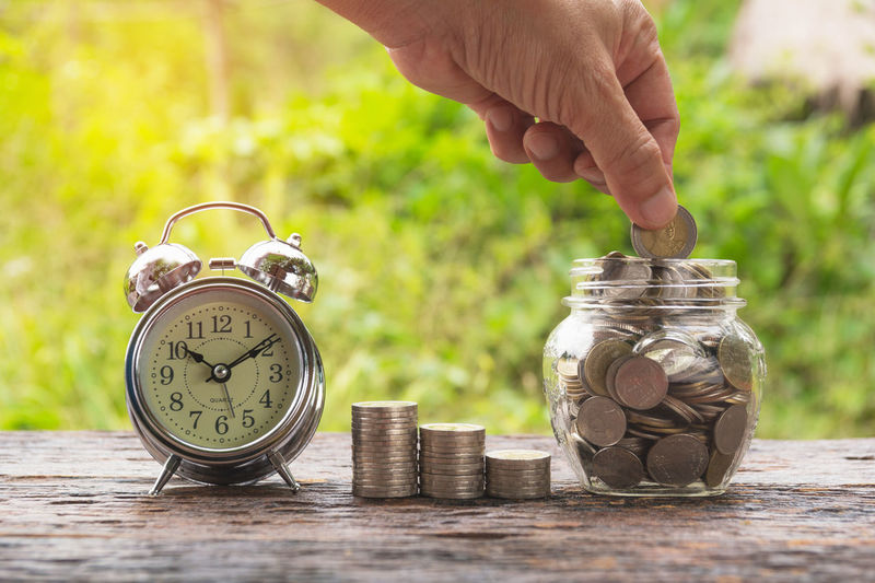 Cropped hand putting coins in jar by alarm clock on table