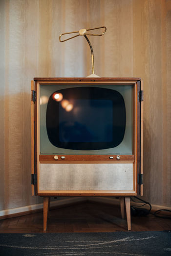 Retro television set against wall at home