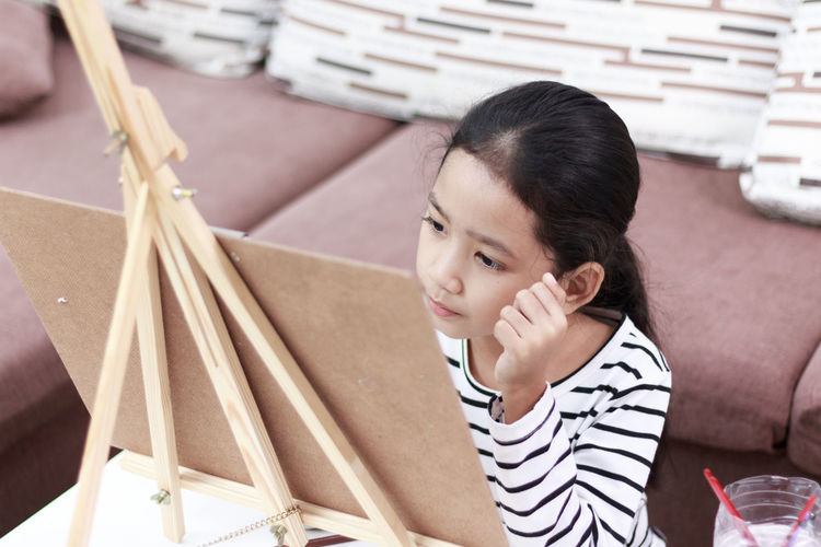 High Angle View Of Girl By Easel