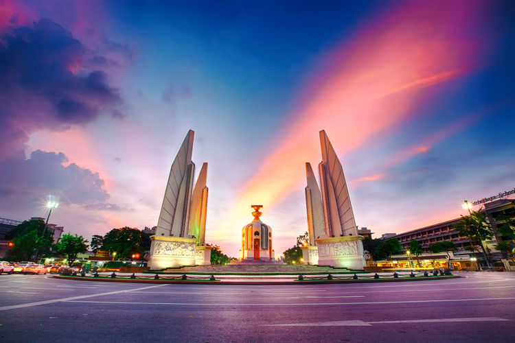 Statue of illuminated temple against sky at sunset