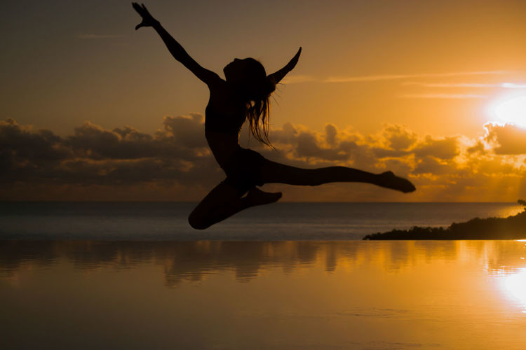 Silhouette woman jumping at sea against sky during sunset