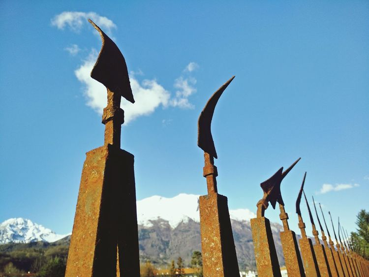 Arrow Art And Craft Bent Blue Cloud Creativity Damaged Day Fence Low Angle View No People Rusty Sky Snowcapped Snowcapped Mountain Snowcapped Mountains Spears Sunlight Landscapes With WhiteWall