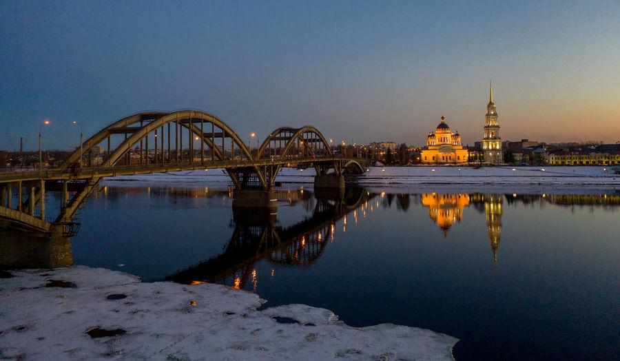 Bridge over river against buildings at dusk