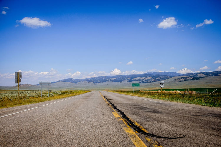 road in the middle of a praire in montana Montana North America Road Trip American West Road Direction Way Forward Movement Moving Travel Traveling Prairies Prairie Sky Transportation The Way Forward Environment Cloud - Sky Empty Road Diminishing Perspective Nature Landscape Mountain Symbol Sign Day No People vanishing point Tranquility Scenics - Nature Country Mountain Range Outdoors Dividing Line Long
