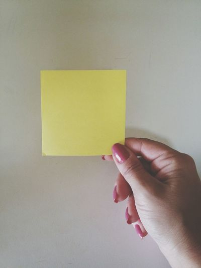 Cropped image of holding adhesive note against gray background
