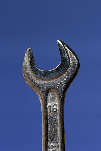 Low angle view of wrench against clear blue sky