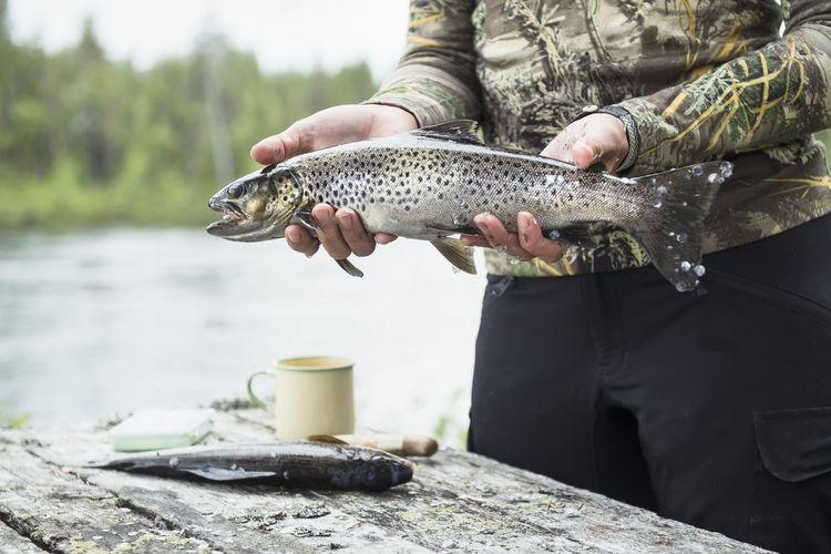 Man holding fish at lake