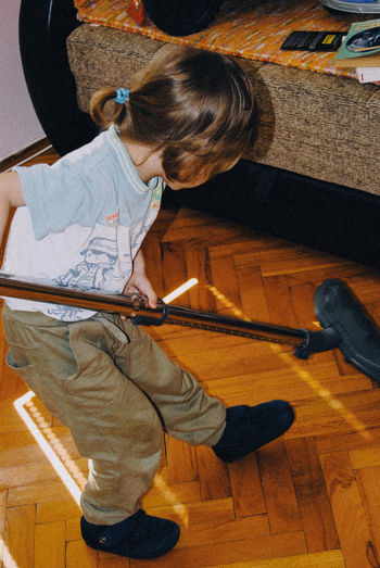 Full length of boy using vacuum cleaner on floor at home