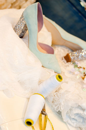 Close-up of shoes and spools with wedding dress