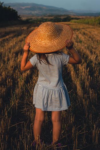 Rear view of woman wearing hat on field