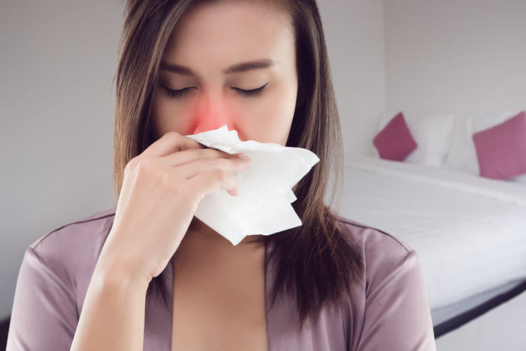 Close-up of young woman blowing nose with tissue paper at home