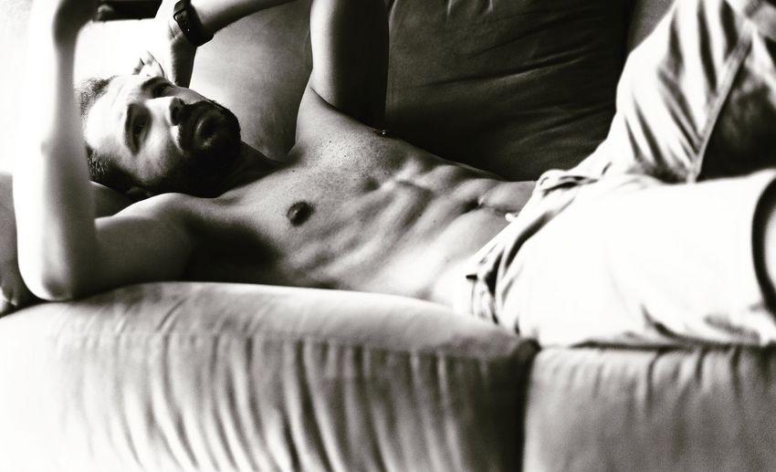 Close-Up Of Shirtless Man Lying Down On Sofa