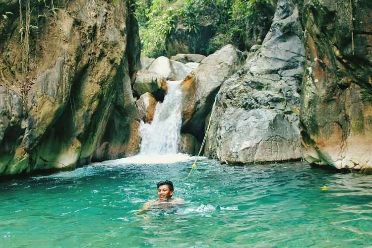 Mid adult man swimming in river amidst rock formation at forest