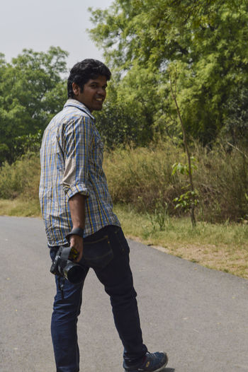 Side view of young man standing on road