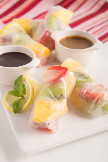 Close-Up Of Fruit Spring Rolls Served On Plate At Restaurant Table