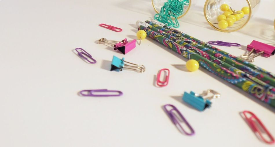 Office supplies spilled over white desk Close-up Collection Macro Multi Colored No People Table Paper Clip Crafts Large Group Of Objects Arrangement White Background Desk Blogger Binder Clips Teacher Push Pins Typography Friendly Text Space Cute Lifestyles Blue Pink Yellow Green Pencils