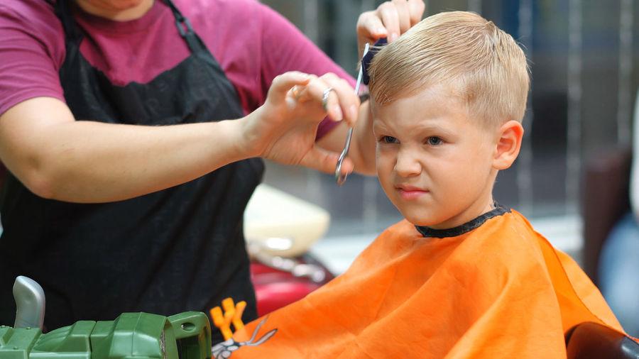 Close-up of boy getting haircut at barber shop