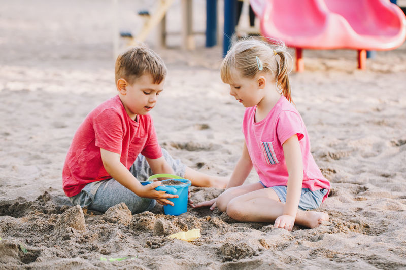 Children playing with toys on sand at beach