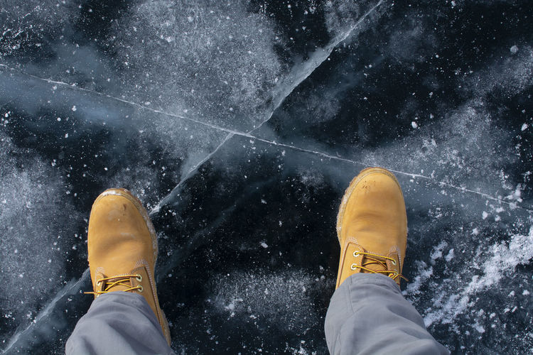 Lake Bikal, Russia Shoe Cold Temperature Human Body Part Human Leg Body Part Snow Personal Perspective One Person Low Section Winter Real People Lifestyles Yellow Leisure Activity Nature Directly Above Men Outdoors Human Foot Human Limb Jeans Snowing