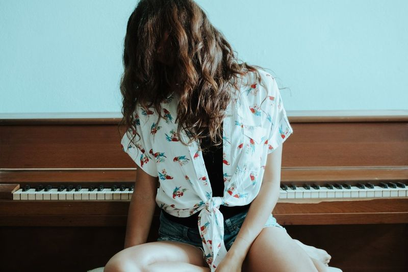 Woman with tangled hair sitting by piano at home