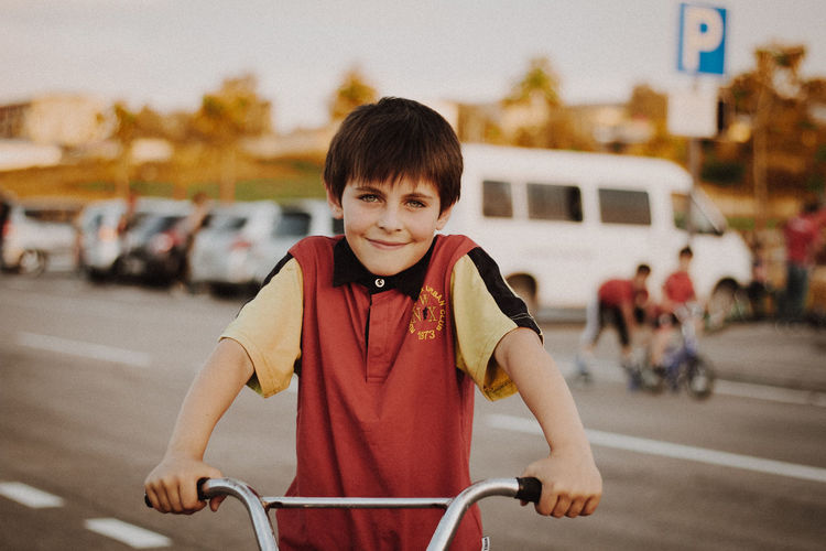 Portrait of boy riding bicycle on road in city