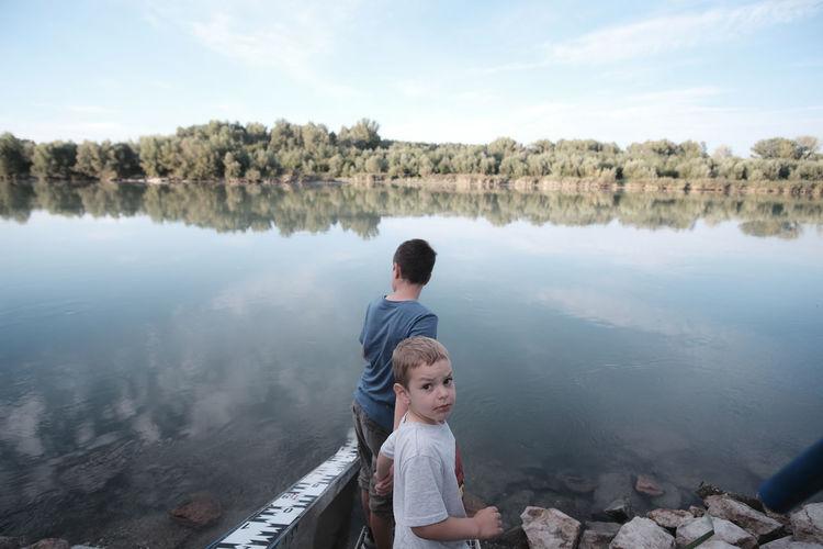 Full length of boys on lake against sky