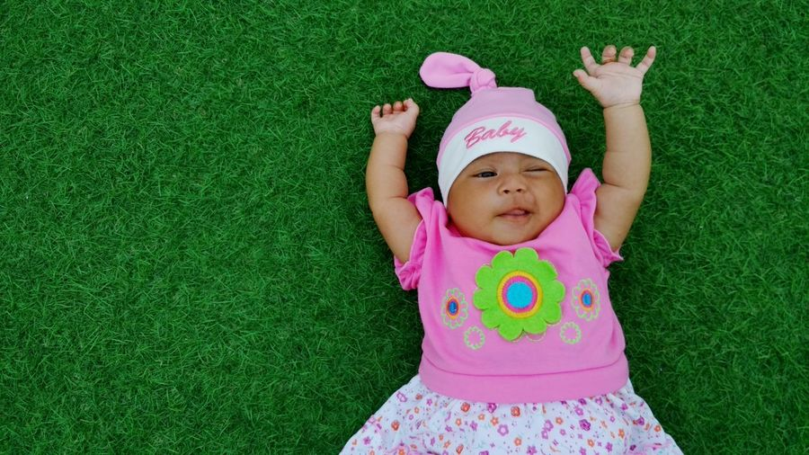 High angle view of baby girl lying on grass