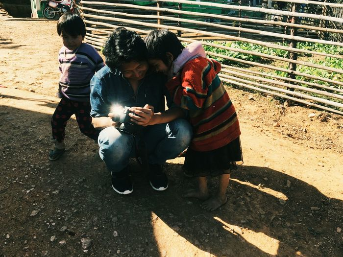 Men Real People Crouching People Day Lifestyles City Sunlight Adult Two People Togetherness Males  Women High Angle View Family Casual Clothing Full Length Females Child Social Issues Chin, Myanmar