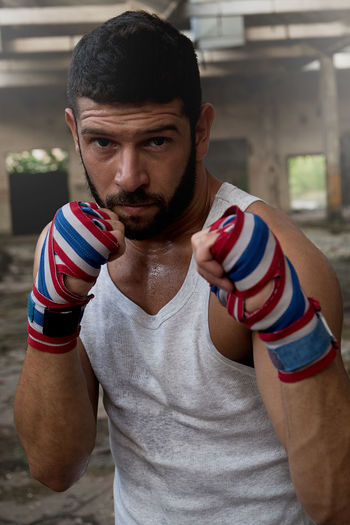Portrait of muscular male boxer posing in boxing stance inside abandoned building. Boxer Beauty Boxing Pose Boxing Stance Close-up Fist Indoors  Lifestyles Looking At Camera One Person People Pose Punch Real People Self Defense Strenght Strength Young Adult
