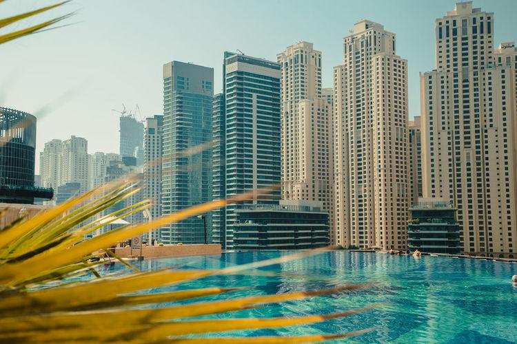 Modern buildings by swimming pool in city against sky