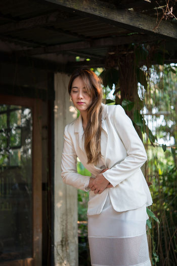 Young businesswoman with stomachache standing outdoors
