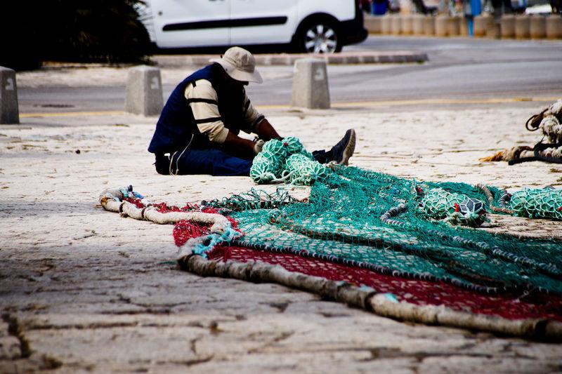 Man sitting by fishing net on footpath