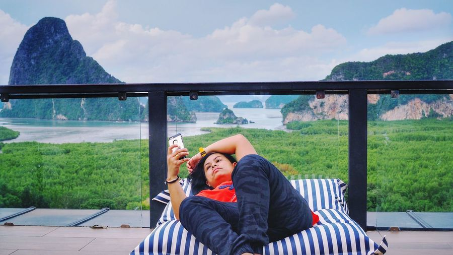 Mature woman using mobile phone while lying on mattress in balcony