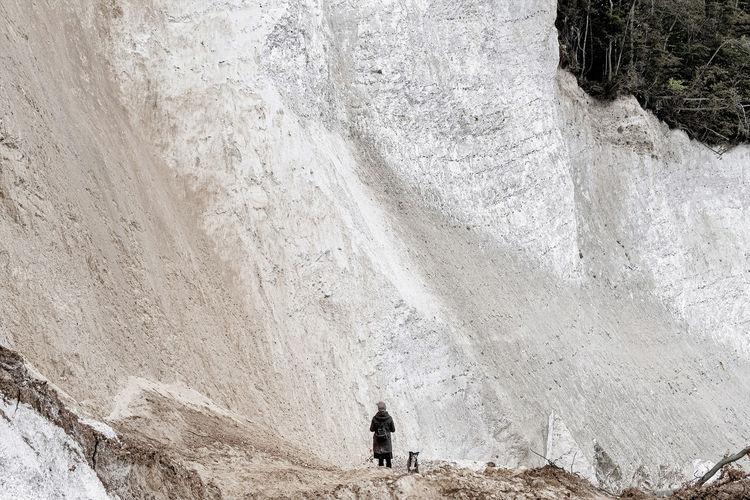 Rear view of men standing on rock