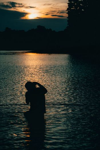 Silhouette man standing by lake against sky during sunset