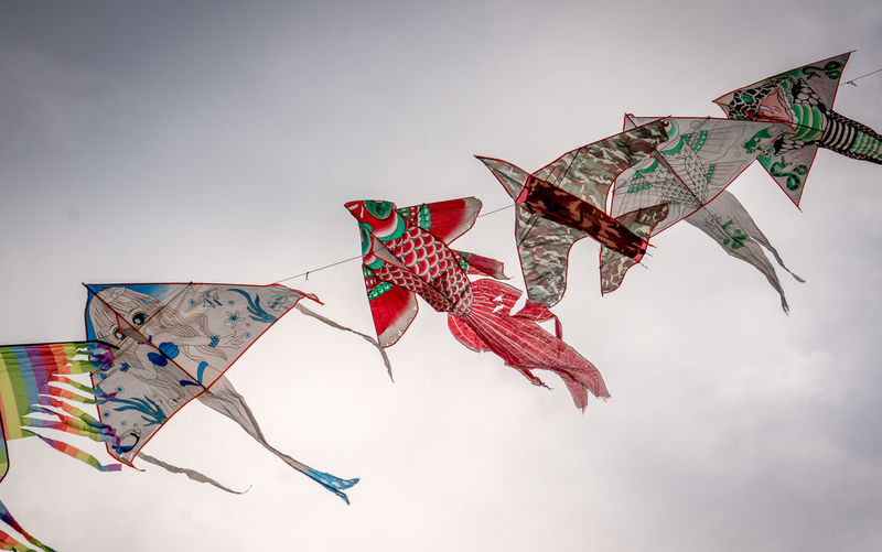 Kites Art And Craft Decoration Environment Hanging Kite - Toy Low Angle View Multi Colored No People Pattern Representation Shape Sky Streamer Wind
