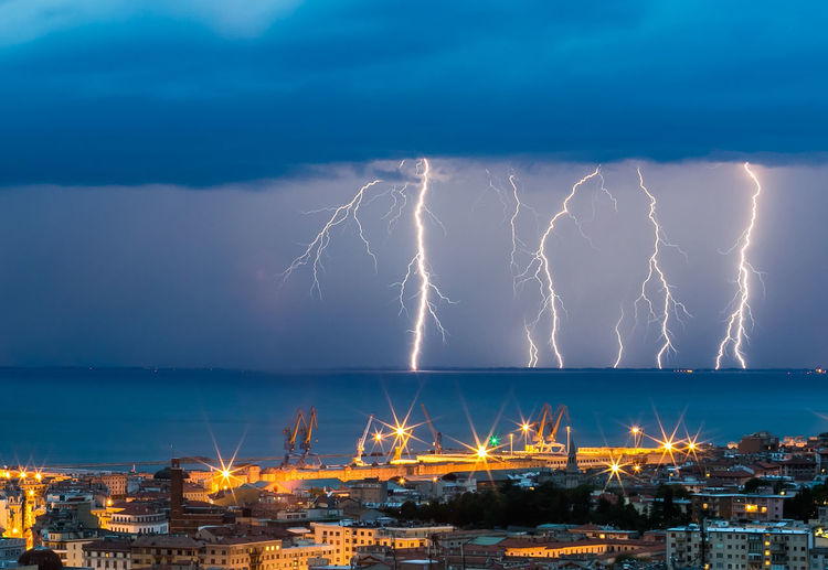 Lightning over sea against city at night