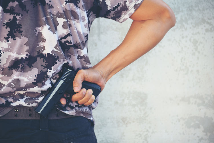 Midsection of man holding gun while standing in front of wall