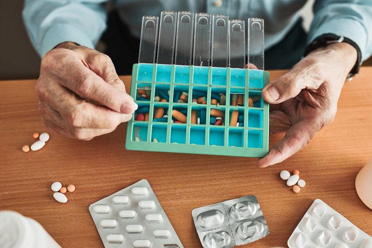 Senior man organizing his medication into pill dispenser. senior man taking pills from box