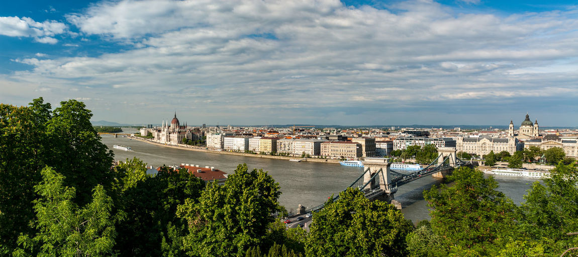 Panoramic view of city by river against sky