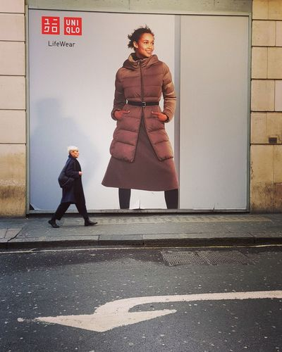 Full length of woman standing against wall in city