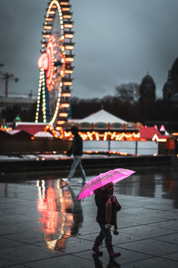 Amusement Park Child City Holding Illuminated Lifestyles Motion Nature Outdoors People Protection Rain Rainy Season Real People Security Umbrella Water Wet