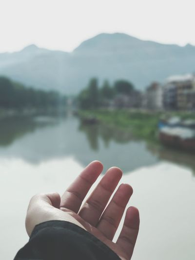 Cropped image of man hand against lake