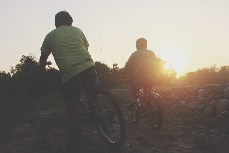 Rear View Of Man And Boy Riding Bicycles On Field During Sunset