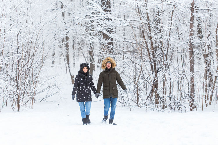 Full length of friends standing on snow covered land