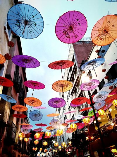 Low angle view of lanterns hanging in market against sky