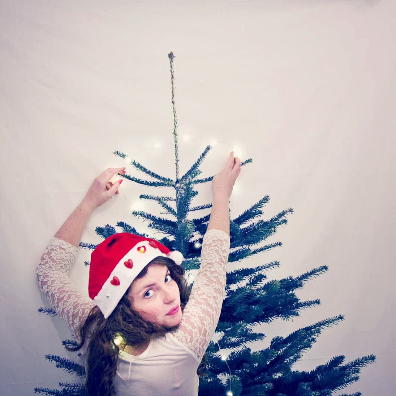 Woman decorating christmas tree over white background