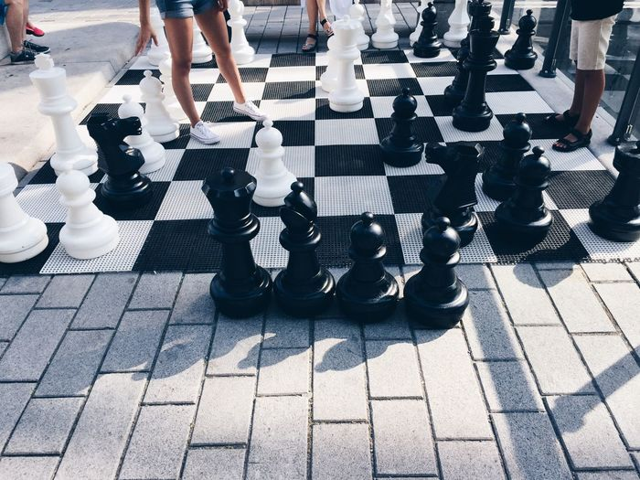 Low section of people standing chess floor