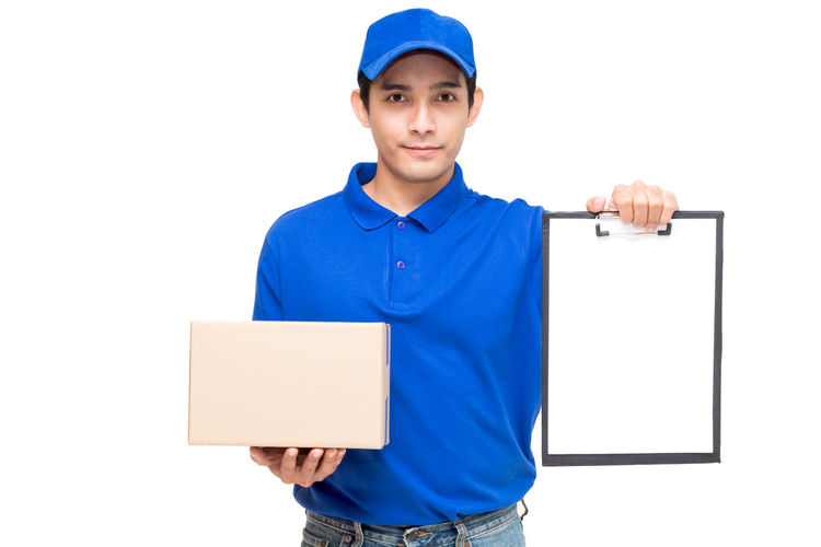 Portrait of salesman holding cardboard box and clipboard while standing against white background
