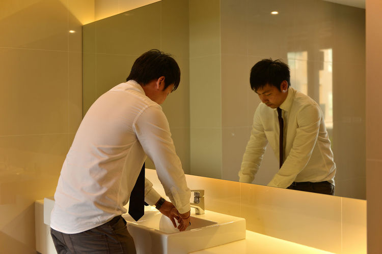 Businessman washing hands in bathroom